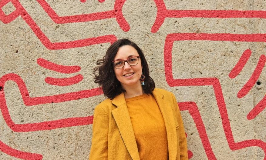 Alice Orrù Copywriter Italiana a Barcellona: una ragazza vestita di giallo ocra posa di fronte a un'opera di street art di Keith Haring