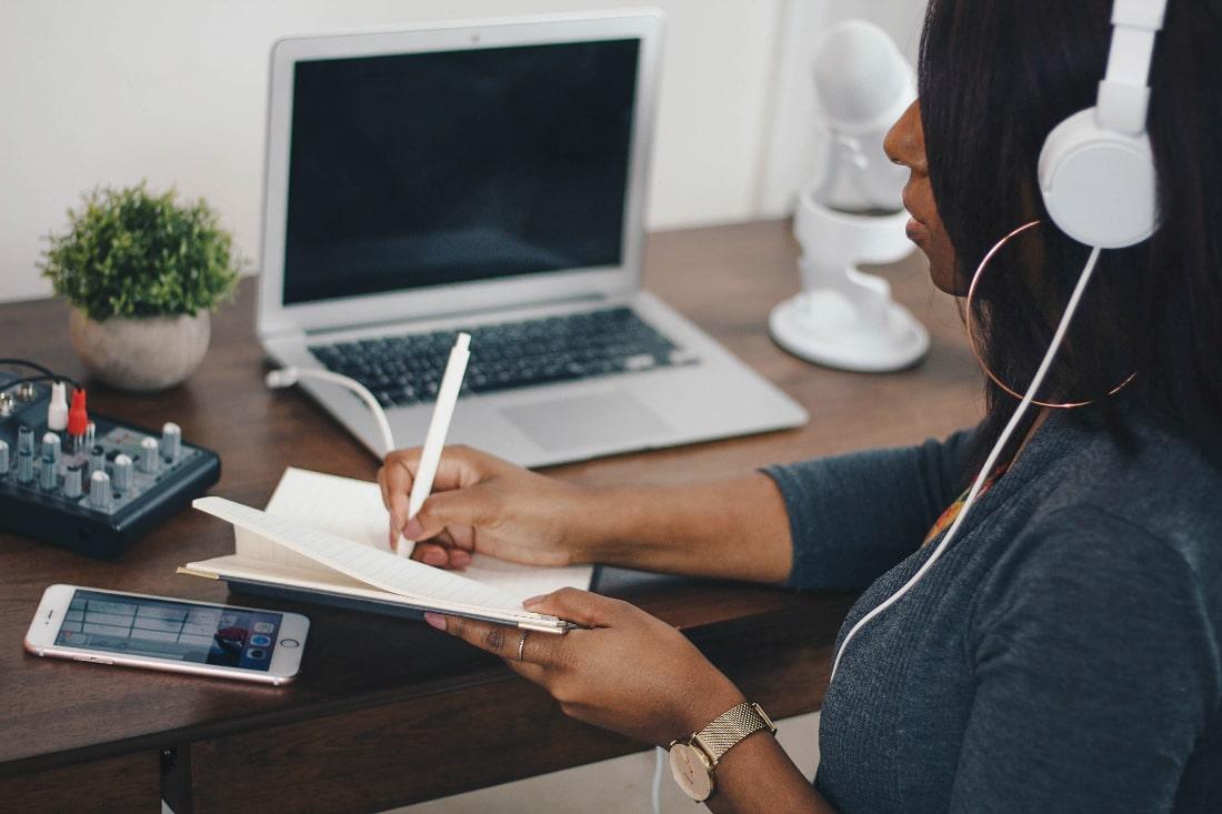 Una ragazza con cappelli neri e golfino grigio scrive su un quaderno mentre ascolta qualcosa con le cuffie