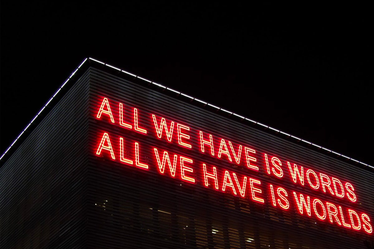 "Scritta al neon rossa: ""All we have is words, all we have is worlds"""