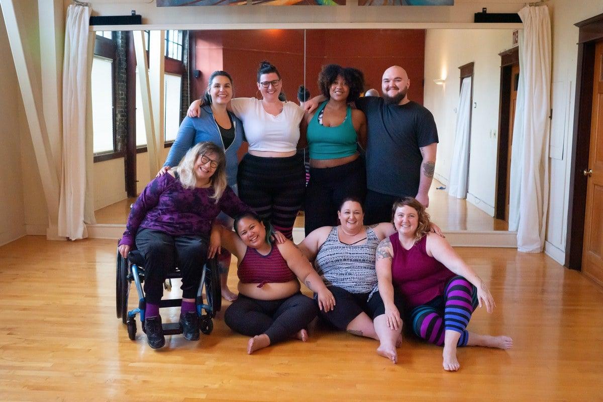 Gruppo di persone eterogeneo che posa in un'aula di yoga