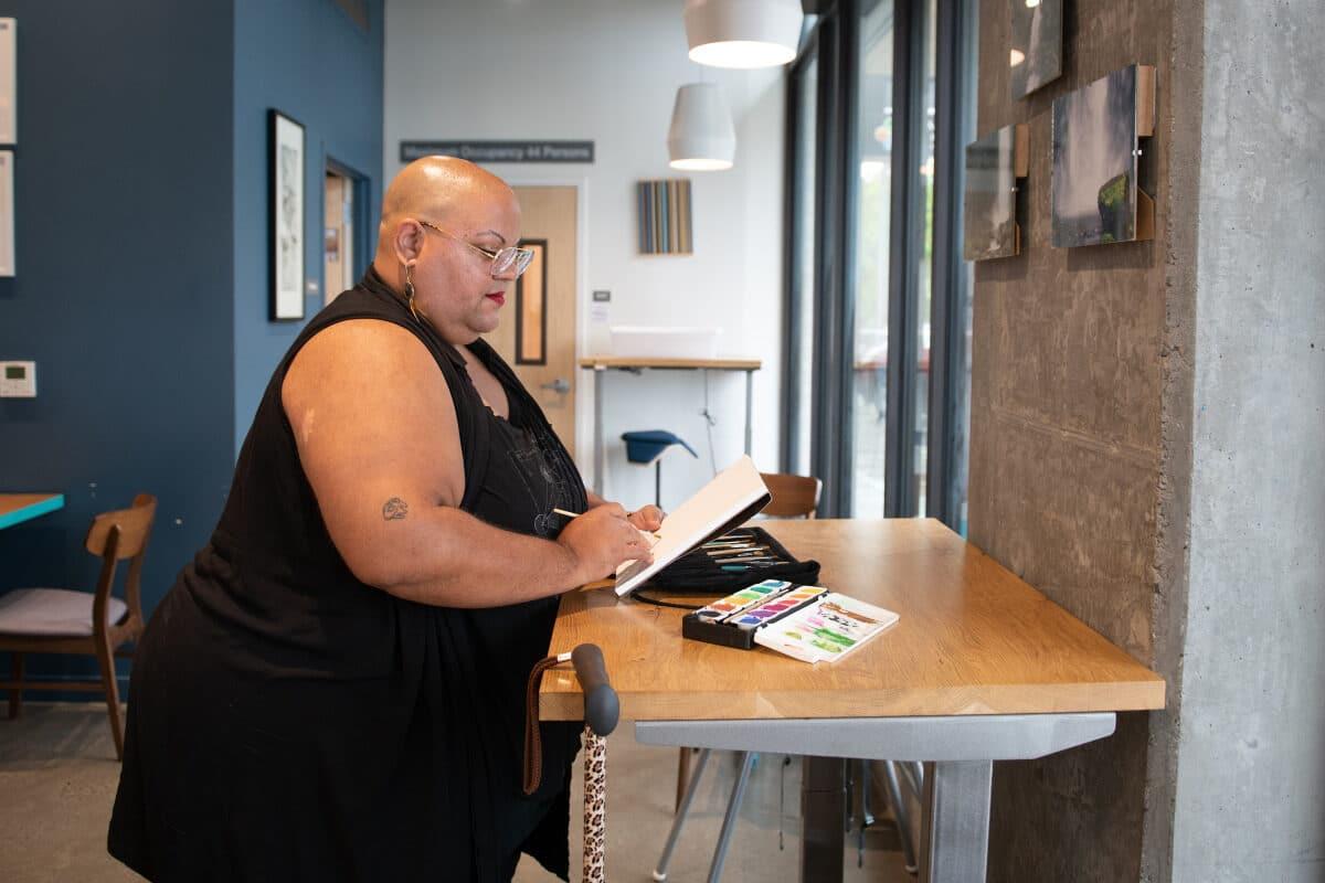 Una persona nera non binaria siede a un tavolo regolabile di una caffetteria e dipinge con gli acquerelli. È vestita di nero, porta occhiali, orecchini e labbra dipinte di rosso, ha la testa rasata. Il suo bastone leopardato è appeso a un lato del tavolo.