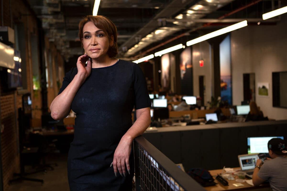 Una donna transgender in abito da lavoro nero nel suo ufficio open space