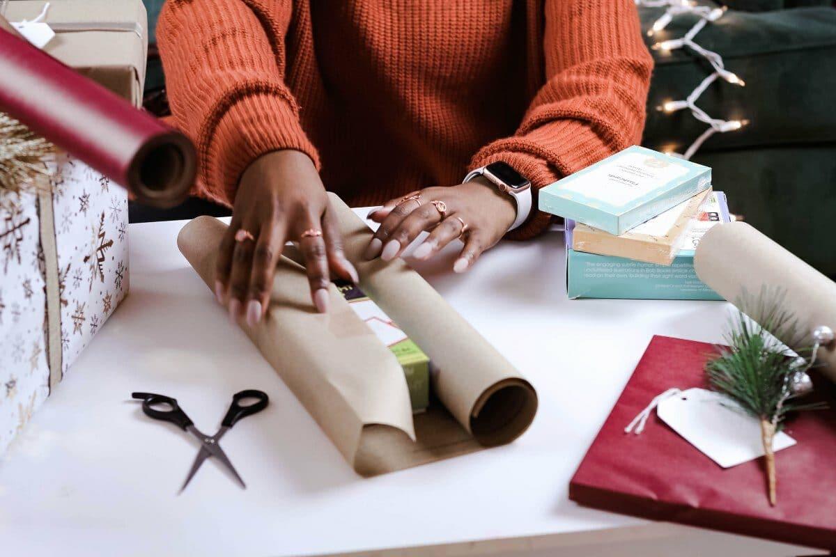 Mani con unghie smaltate di rosa di donna nera che indossa un maglione arancione. La persona sta avvolgendo una scatola nella carta regalo.