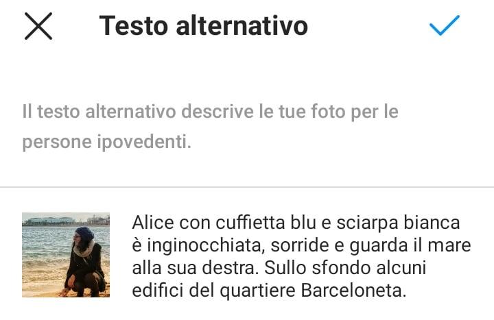 La schermata per aggiungere il testo alternativo su Instagram. L'alt-text di questa foto è: Alice con cuffietta blu e sciarpa bianca è inginocchiata, sorride e guarda il mare alla sua destra. Sullo sfondo alcuni edifici del quartiere Barceloneta.