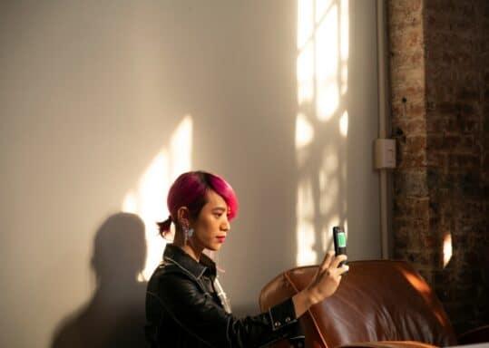 Una persona con i capelli rosa che si scatta un selfie con il telefono
