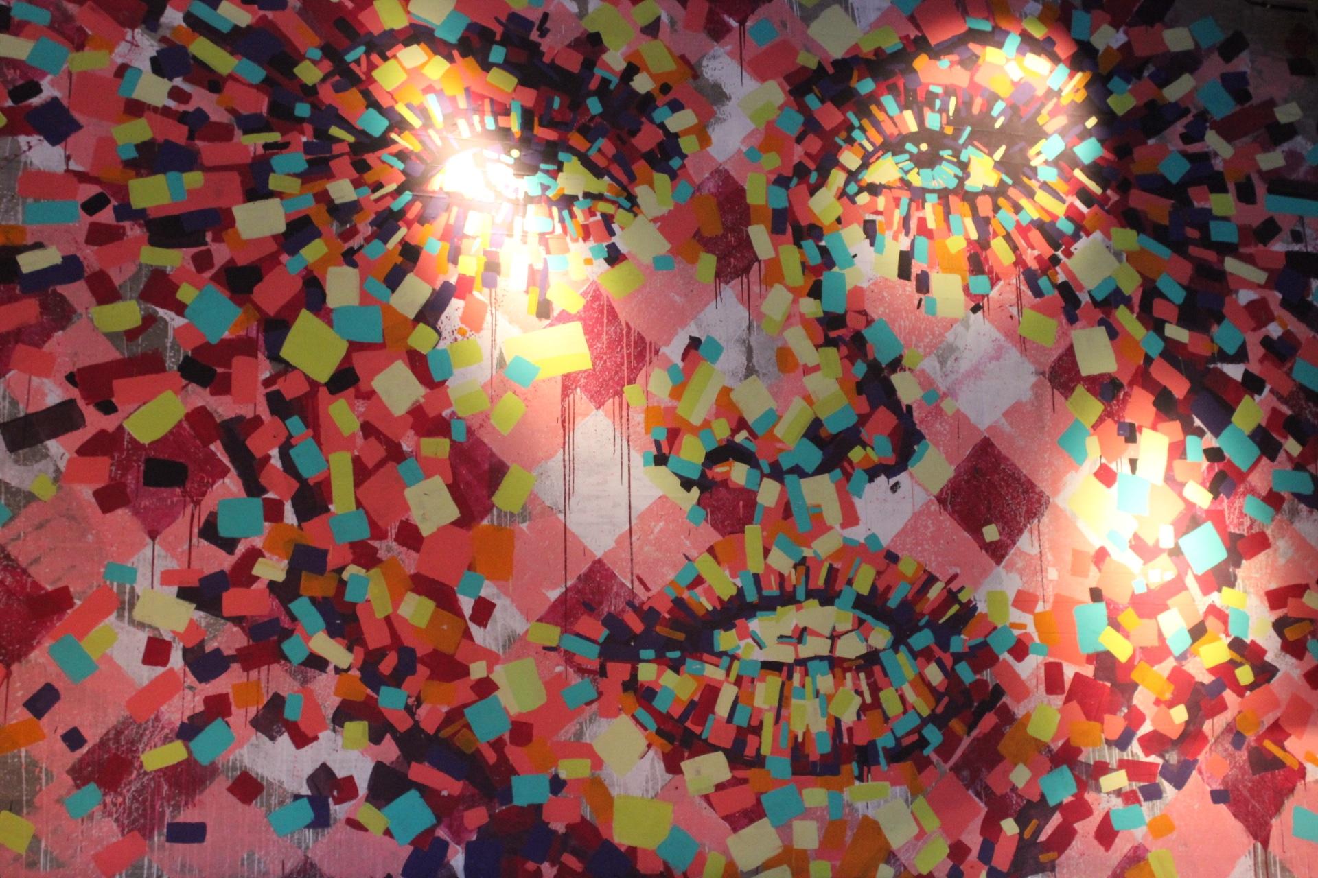 Un'opera di street art a Buenos Aires: il volto di una persona ricostruito con quadrati di ogni colore su sfondo rosso e rosa