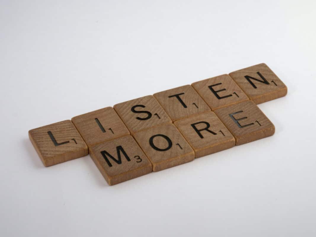 """Tasselli di legno del gioco Scarabeo poggiati su sfondo bianco. La scritta dice """"Listen more""""."""
